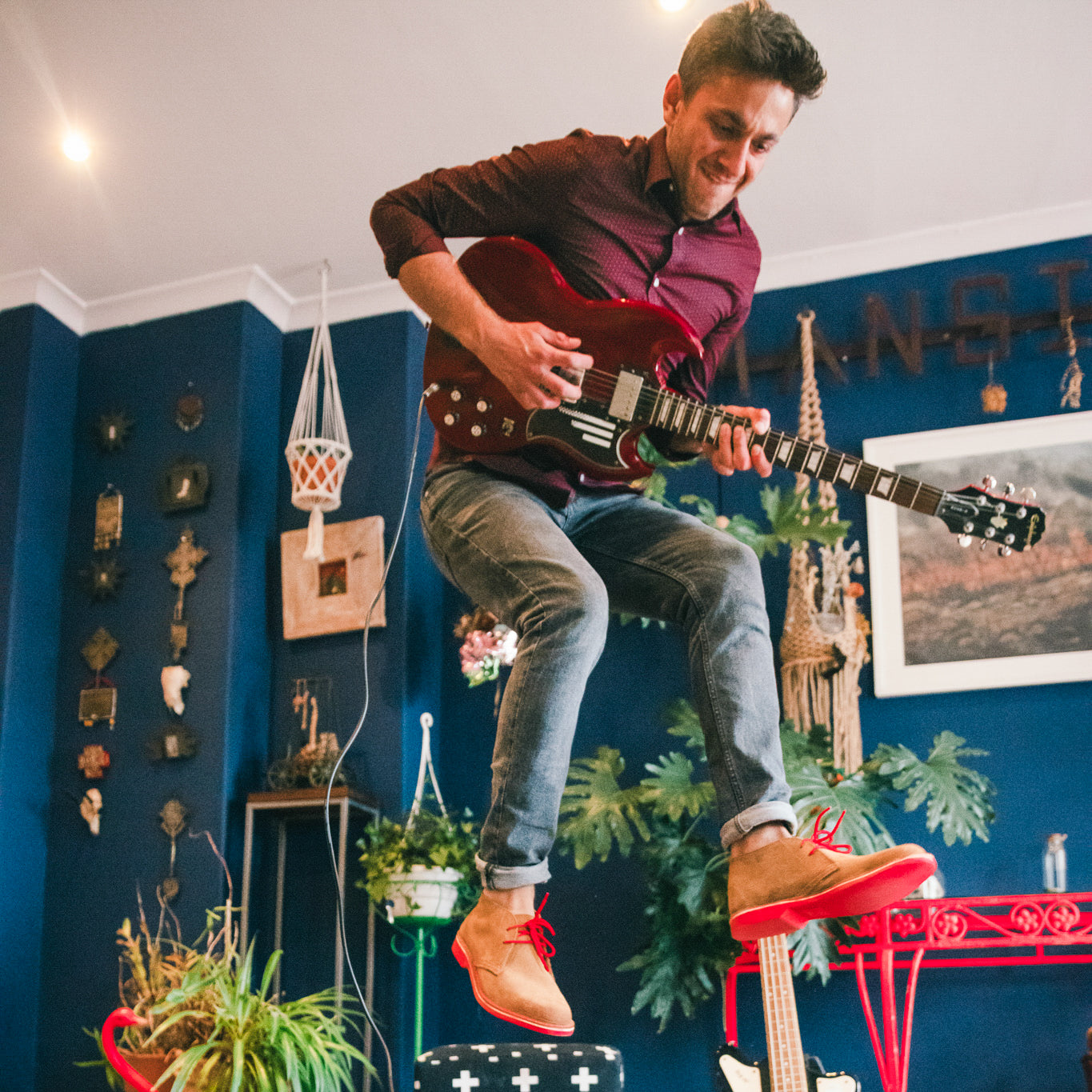 Veldskoen shoes and boots or known as vellies heritage boot ethically and sustainably handcrafted in South Africa sold in united states man weraing red laced suede heritage and jumping high in the air playing guitar