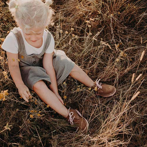 You child sitting in grass wearing pink Veldskoen shoes ethically handcrafted genuine leather boots and shoes from South Africa