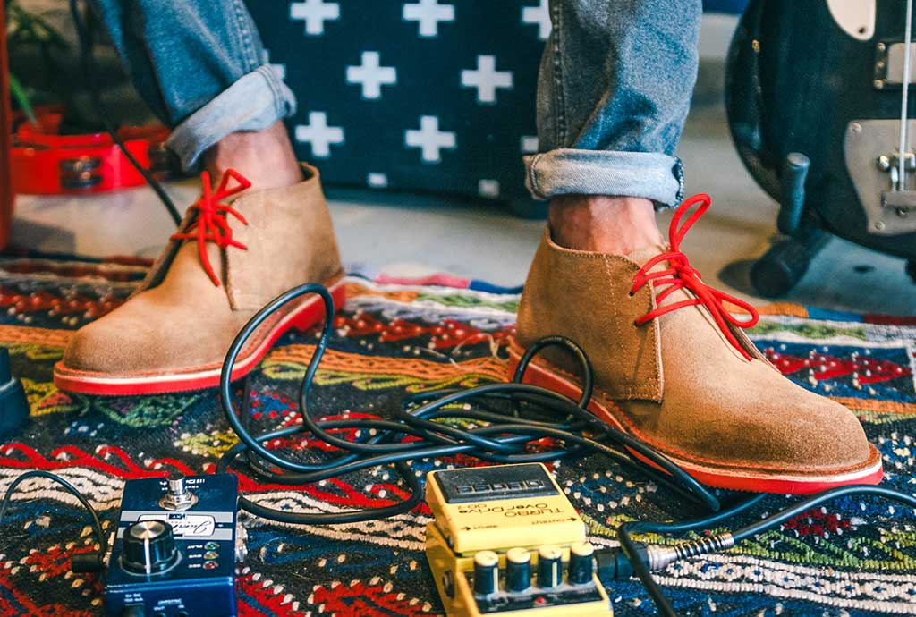 Man wearing red Veldskoen shoes ethically handcrafted genuine leather boots and shoes from South Africa heritage mens veldskoene original suede chukkas in red with musical stuff around guitar