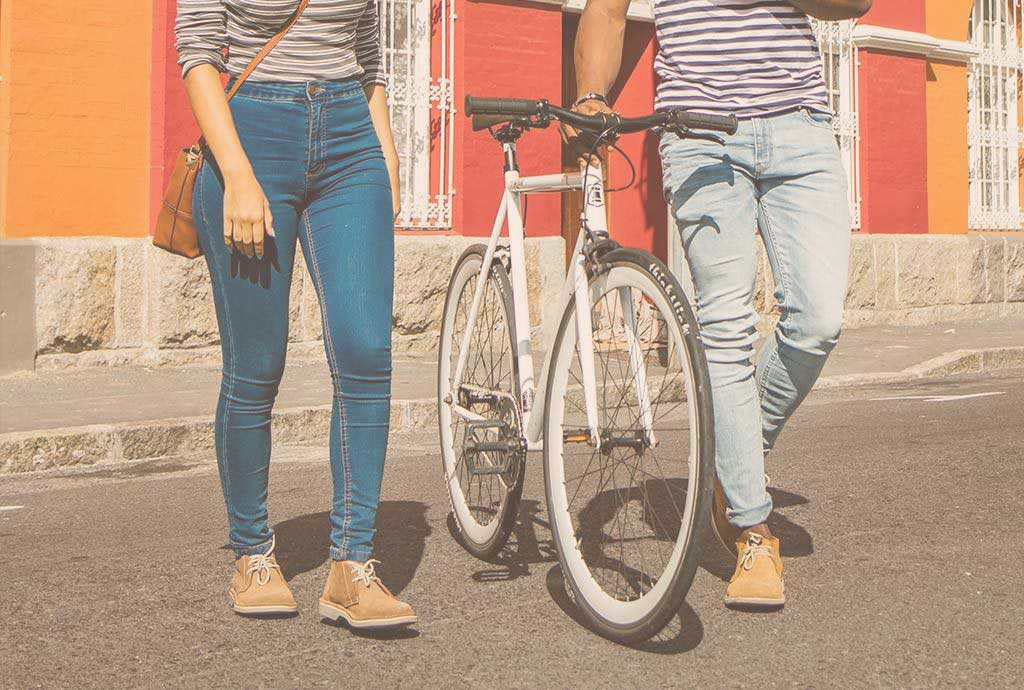 couple on bike with colorful buildings in jeans and black veldskoen at coffee chop with women in red dress wearing pinotage suede Veldskoen shoes ethically handcrafted genuine leather boots and shoes from South Africa