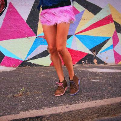 Women in pink feather mini skirt wearing vellies Veldskoen shoes ethically handcrafted genuine leather boots and shoes from South Africa