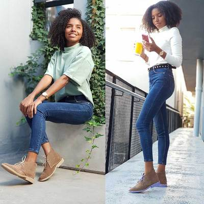Women holding phone and yellow coofee cup in tight jeans and wearing vellies purple sole Veldskoen shoes ethically handcrafted genuine leather boots and shoes from South Africa
