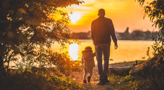 Father and child walking hand in hand towards a body of water with a sunset