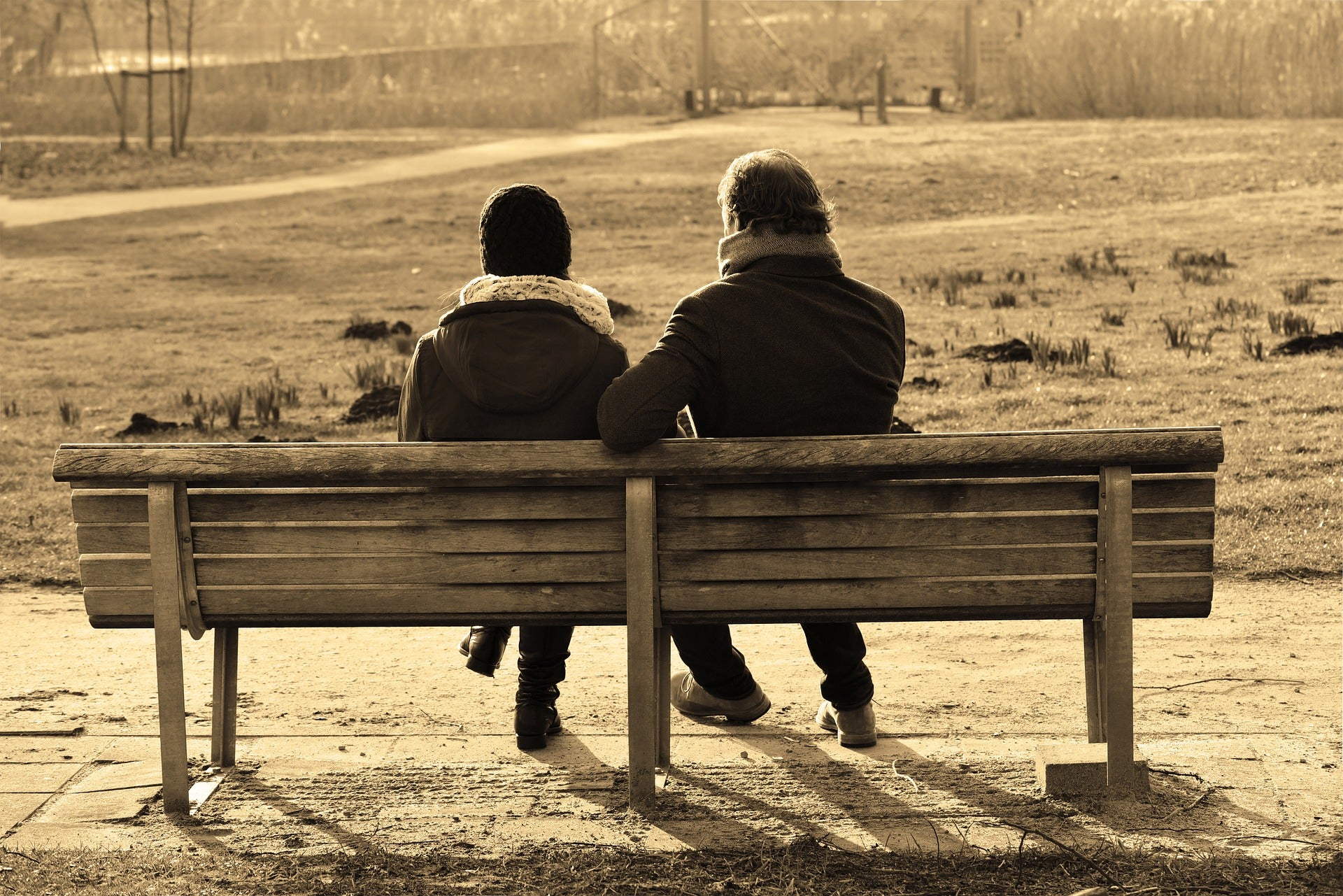 Man and woman in winter clothing sitting on park bench.