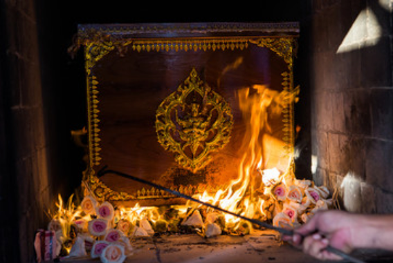 Person lighting incense at the urn site of someone