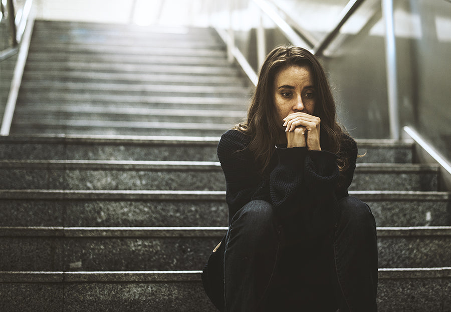 Woman looking worried while sitting on steps