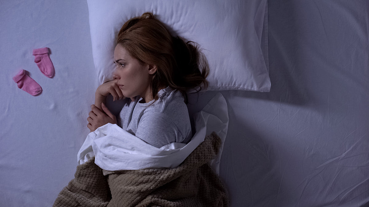 Woman laying bed looking sadly at a pair of infant socks