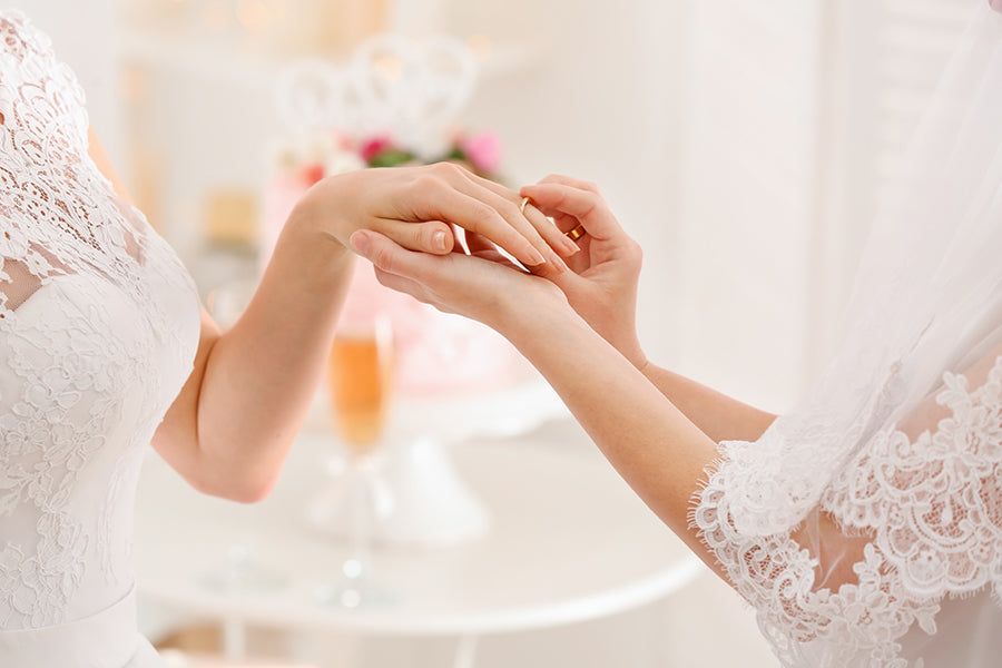 Close up of hands of lesbian wedding couple exchanging rings.