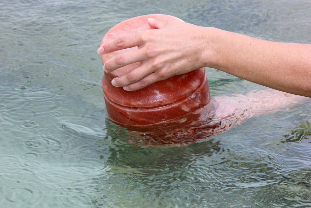 Himalayan rock salt urn being placed in water by two hands.