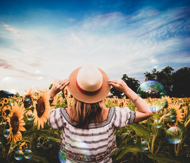 Woman facing away from camera in a field of sunflowers with her hands up holding the brim of her straw hat