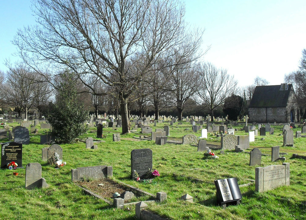 A cemetery with bright green grass and headstones.