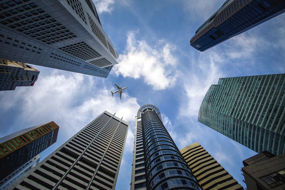 view from below of a plane flying through skyscrapers