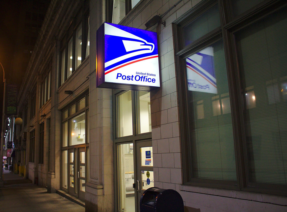 Neon united states postal service sign on the side of a building at night