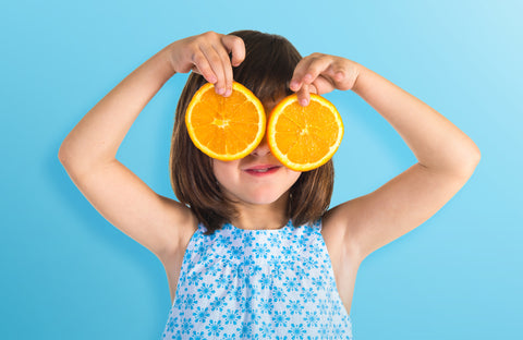 girl, orange, vitamin c, wellvites kids vitamins