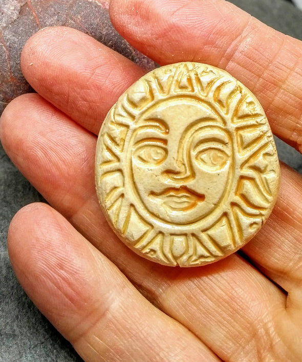 Ceramic sun brooch being held to show size