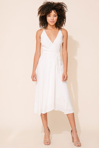 Yumi Kim's City Lights Wrap Midi Dress. This white wedding guest dress includes a snap chest closure, self-tie waist, and adjustable crossover spaghetti straps.
