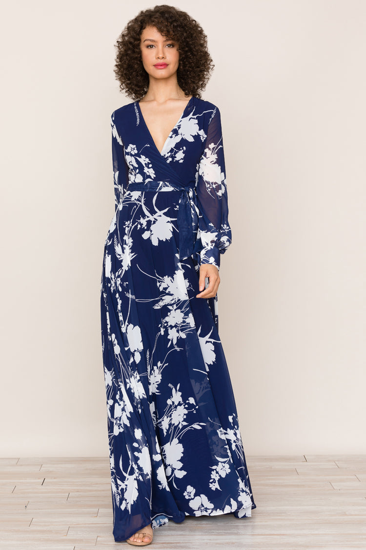 Yumi Kim's Giselle Navy Floral Maxi Dress. The printed dress includes long sleeves, attached belt, a wrap bodice, buttons on cuff, snap closure on neckline, and hidden back zipper.