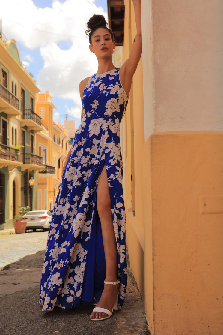 Eye-catching Dream Blue Silk Maxi Dress features a bold floral print and long flowing skirt with a thigh high slit.