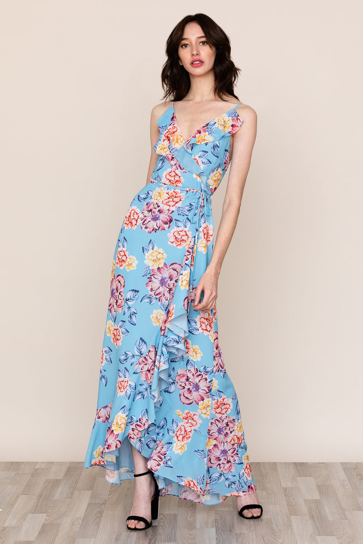 Feminine ruffle details accent the hem and neckline of our wrap style Meadow Floral Ruffle Maxi Dress. Details include adjustable straps and tie closure at waist.