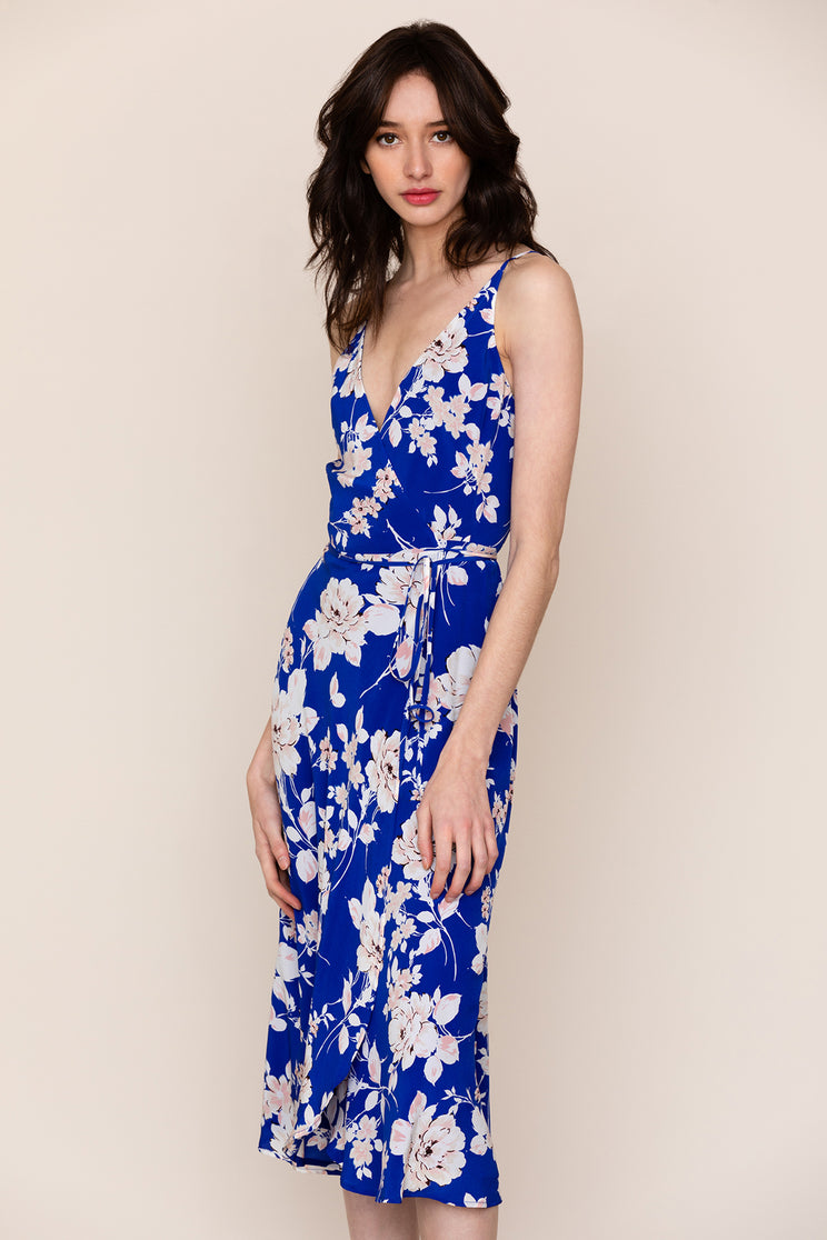 A wrap style silhouette and midi length makes Yumi Kim's City Lights royal blue floral silk dress your new go-to. Details include snap chest closure, self-tie waist, and adjustable crossover spaghetti straps.