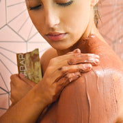 woman in shower using bodibar anti-ageing body scrub and mud mask spa treatment