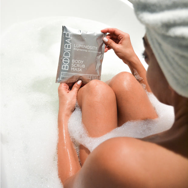 woman in bath holding bodibar luminosity detoxifying body spa mud treatment