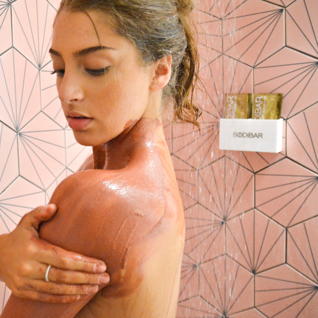 woman using Purity Anti-Ageing mud spa treatment in shower featuring shower caddy holder on shower wall