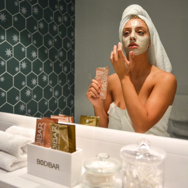applying bodibar intense hydration body scrub and mud mask spa treatment on face