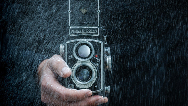 Man's hand holding a camera in the rain.