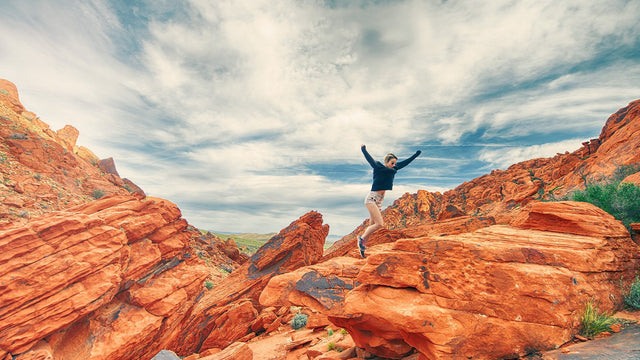 Young woman jumping happily on a rocky red canyon, blue skies in the background..