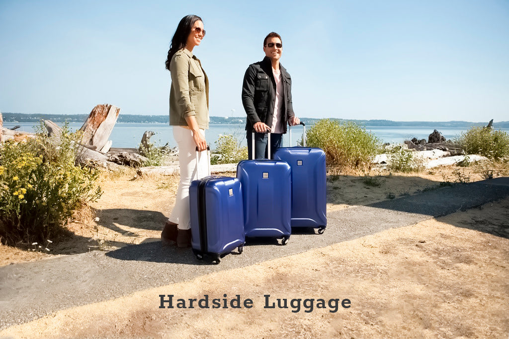 Man and woman standing with their blue hardside luggage set