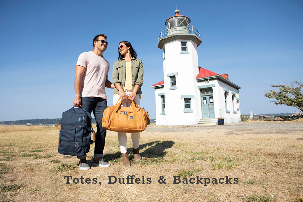 Man and woman standing in front of lighthouse carrying a tote and duffel bag