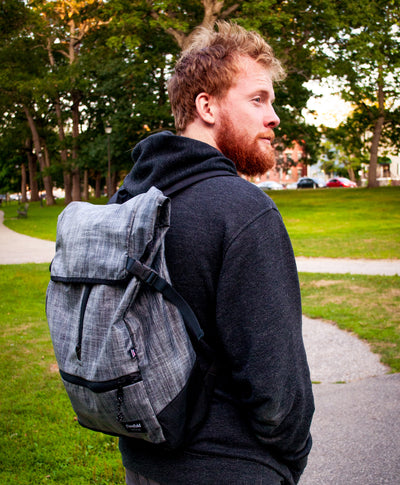 Flowfold Commuter Center Zip Backpack on man on campus