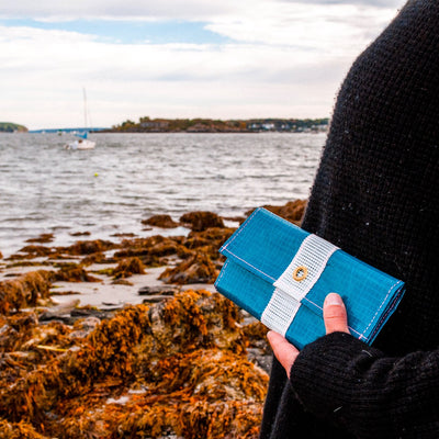 Flowfold x Alaina Marie Cyan/White Seacoast Trifold Wallet clutch in women's hand at seaside