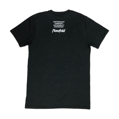 Men's Black Flowfold T-Shirt back view with stacked saying: Craftsmanship, Community, Sustainability, Stewardship