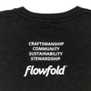 Men's Black Flowfold T-Shirt close up back view with stacked saying: Craftsmanship, Community, Sustainability, Stewardship