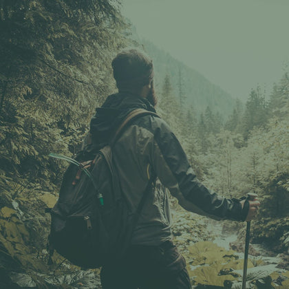 Man hiking in forest with outdoor gear | Summit Creek Shop