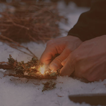 Man lighting campfire outdoors in snow | Summit Creek Shop