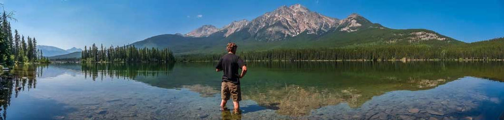 Man in lake looking at mountain summit in nature and forest with a clear day for adventure
