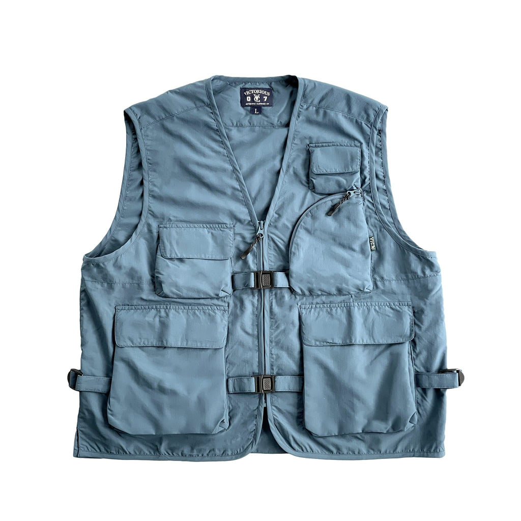 VIC Utility Vest / Inspired by vintage workwear silhouettes : Boxy fit / 100% Polyester, durable water resistant coating / Two way zip closure at front / 5 front pockets / 2 quick release buckles & side closures for layering / Hidden pocket at centre back / VIC woven flag label at front left chest pocket