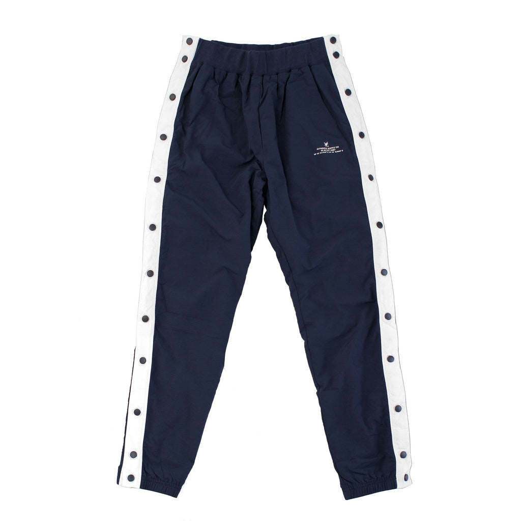 Men's and Women's Warm up tearaway snap track pants in navy by New Zealand skate and streetwear clothing label VIC Apparel. American 90s vintage sportswear style. Slim fit.