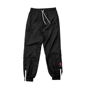 Showerproof nylon swishy track pants in black by New Zealand skate and streetwear clothing label VIC Apparel. Embroidery logo design. American 90s vintage classic sportswear relaxed fit.
