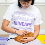 Guinea Pig Held by Woman wearing White GuineaDad T-Shirt With Purple Lettering says Guinea Pig in Sizes Small Medium Large XL