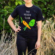 Woman standing around Hay wearing Black GuineaDad T-Shirt with graphic of vegetables and text that read The Veggie Club in Sizes Small Medium Large XL