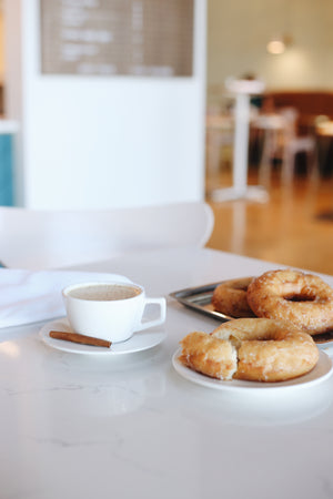 A table set with a specialty coffee and doughnut at Stay Golden's Berry Hill location in Nashville, TN.