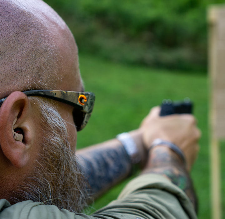 man demonstrating hearing protection device for shooting at the range