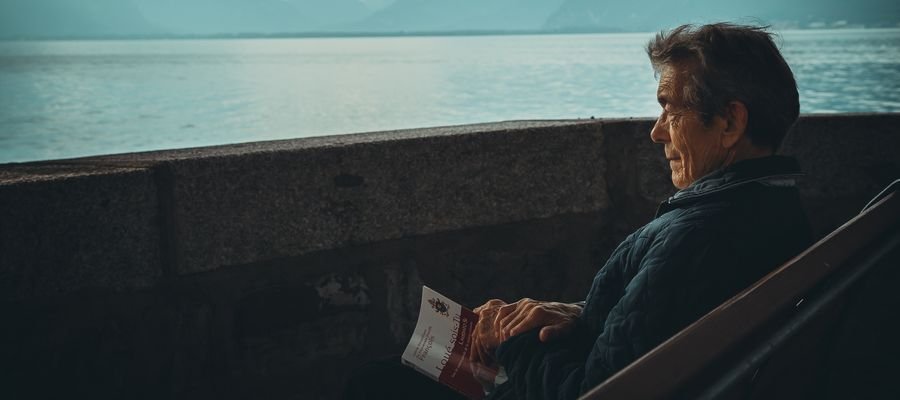 senior man looking out at the sea with book in hand