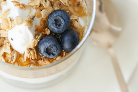 blueberries with cereal for breakfast in white bowl closeup