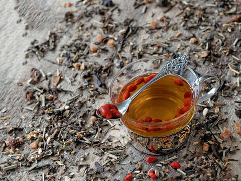 Cup of goji berry tea with spoon holding gojis