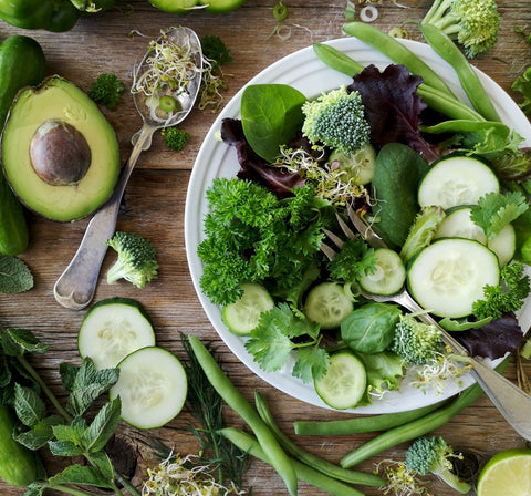 leafy greens in white bowl and on table